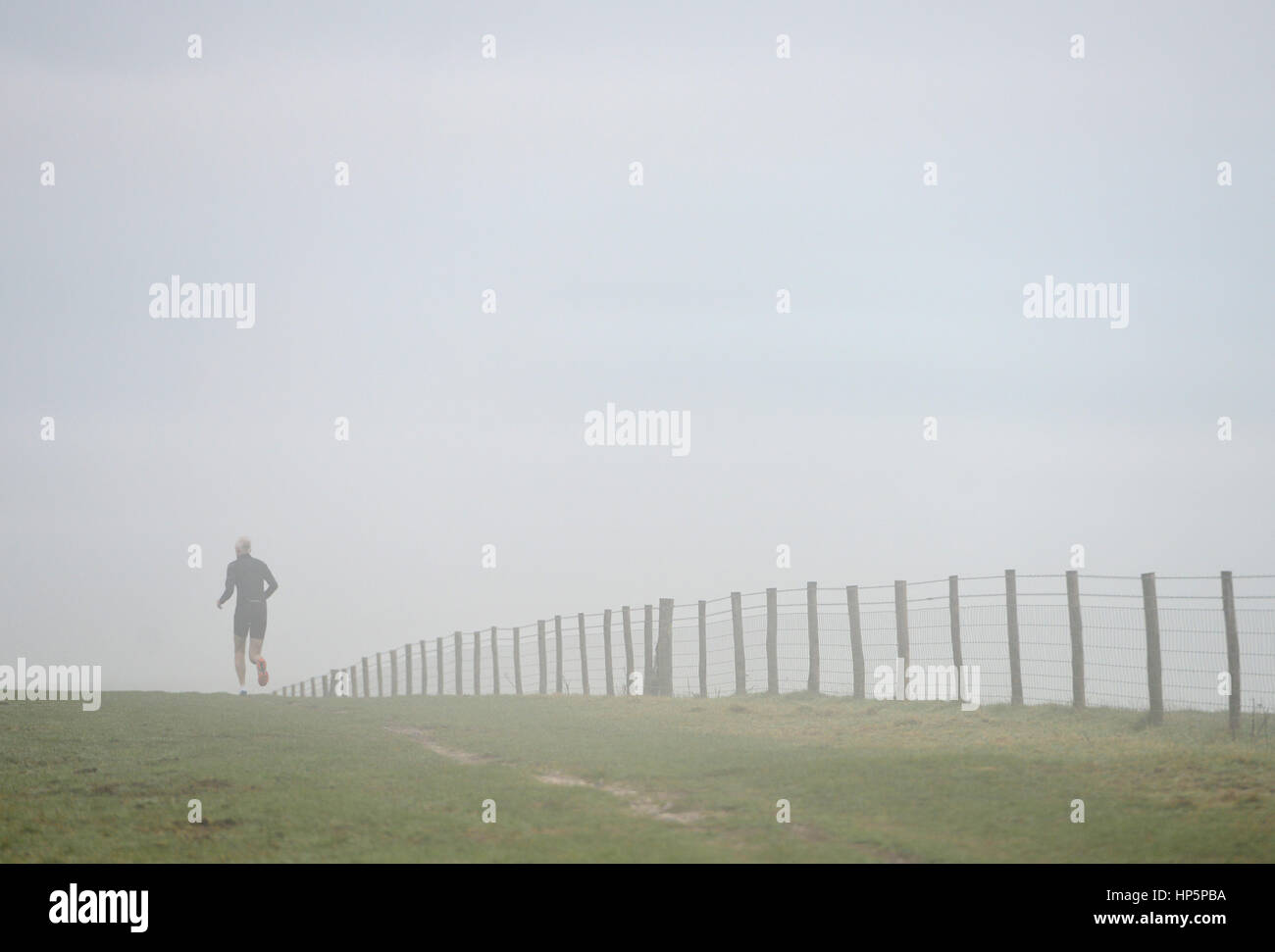 South Downs National Park, East Sussex. 19th February 2017. Morning mist surrounds a runner on the South Downs national - Stock Image