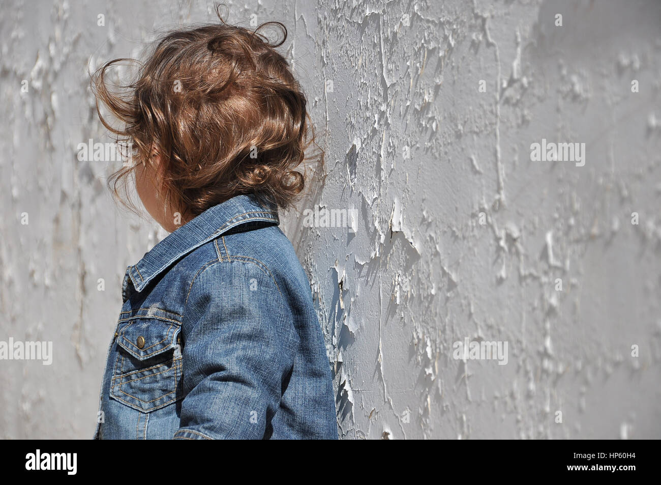 Little baby todller standing in front of a white background wall - Stock Image