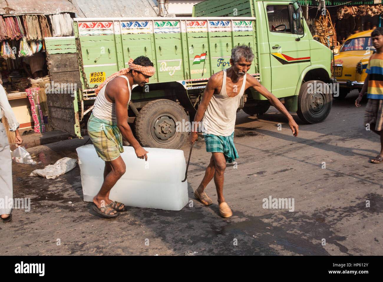 Huge,blocks,of,ice,being,transported,over,filthy,floor,at,Hogg Market,Kolkata,Calcutta,West Bengal,West,Bengal,India,Indian,Asia,Asian, - Stock Image