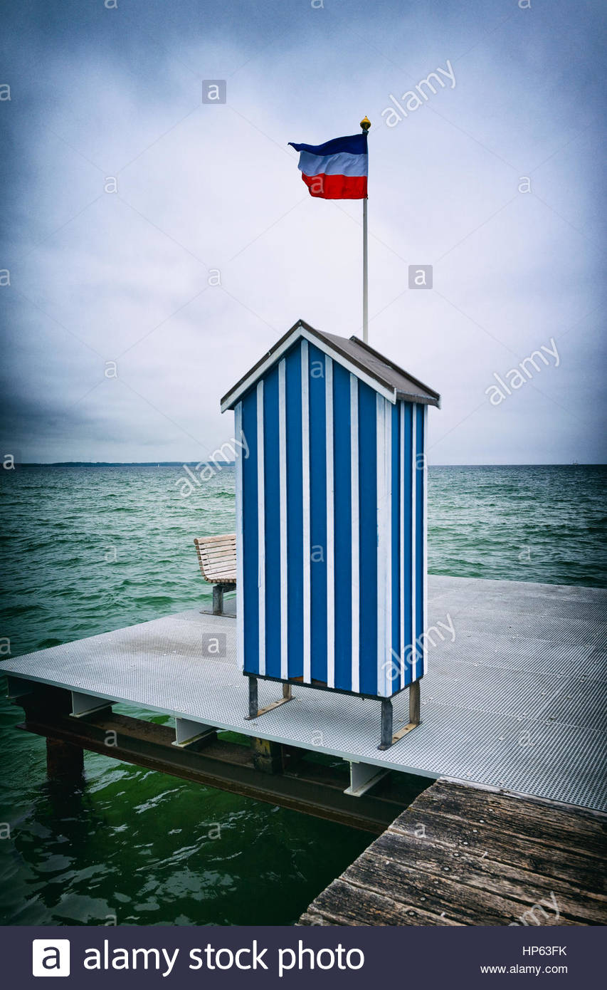 Pier ocean changing cabin blue stripped flagpole - Stock Image
