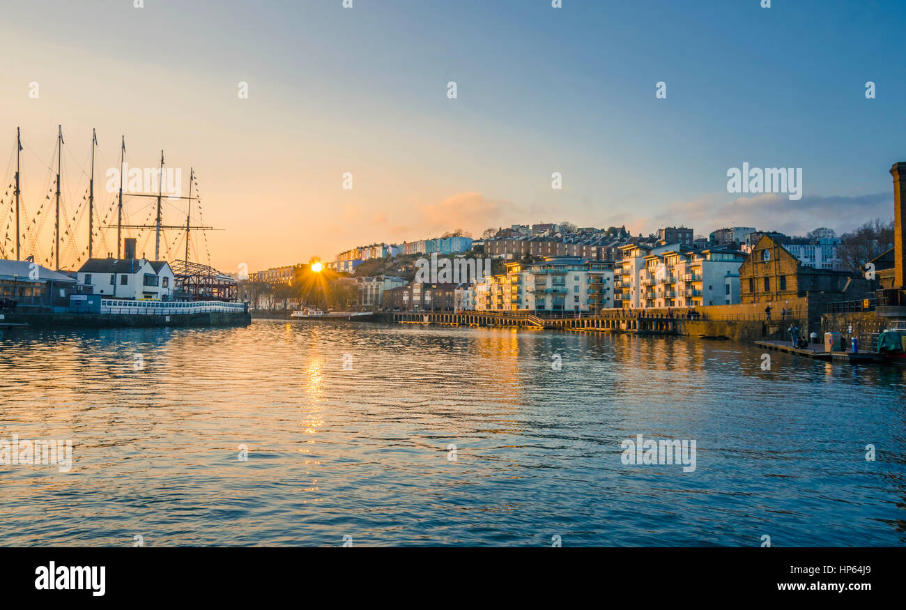 The sun sets behind the horizon casting an orange glow over Bristol Harbour in the UK. - Stock Image