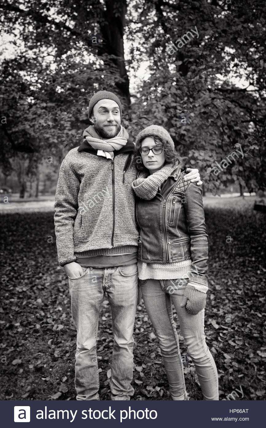 Young heterosexual couple autumn flirting 20s tree - Stock Image