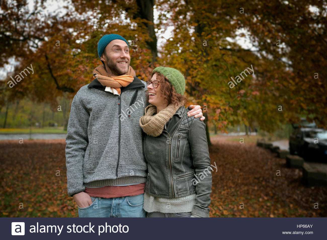 Young heterosexual couple autumn laughing 20s tree - Stock Image
