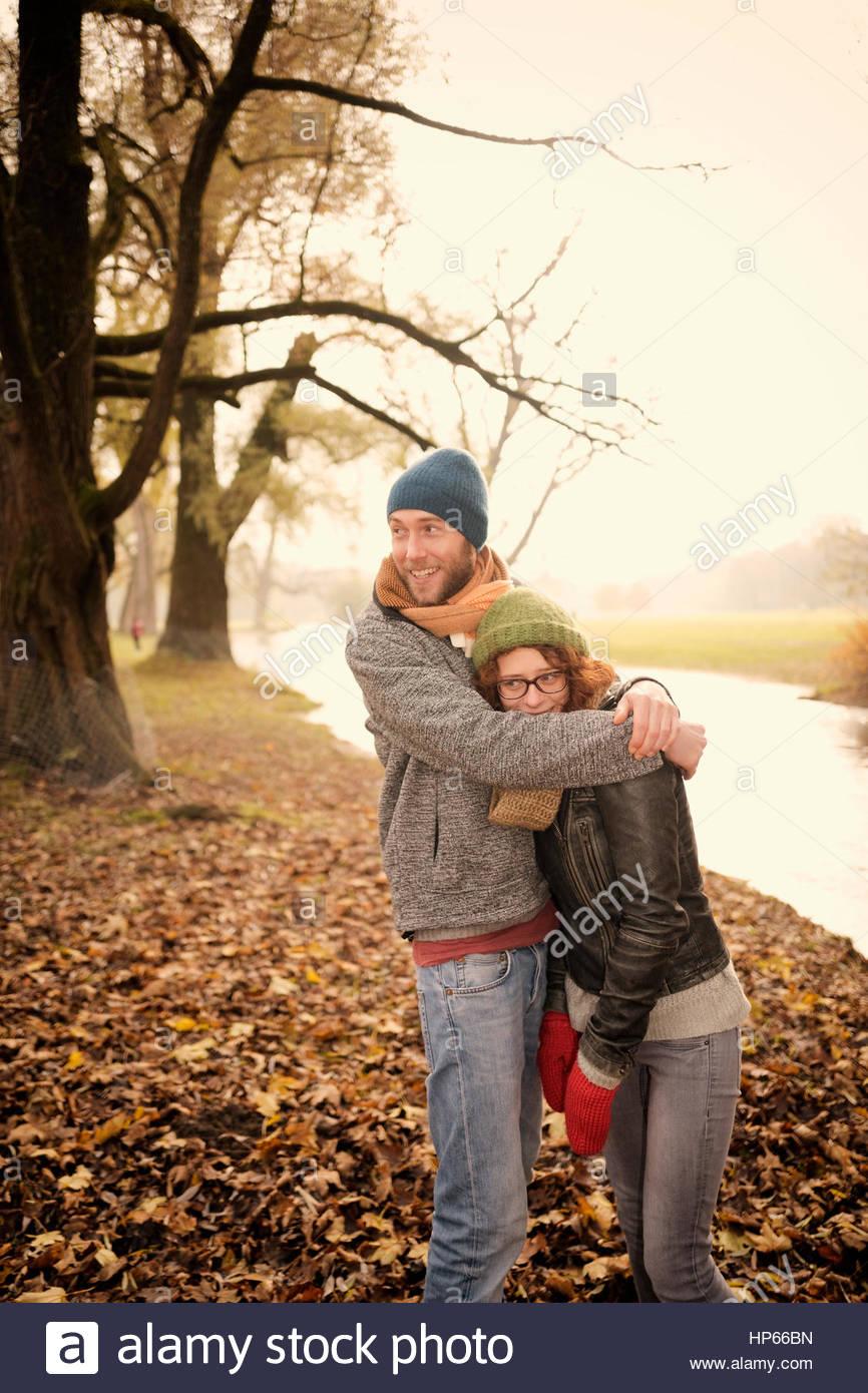 Heterosexual couple autumn hugging embracing fun - Stock Image