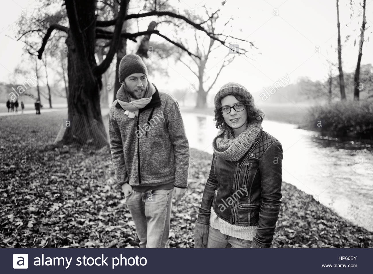 Young heterosexual couple autumn leaves river 20s - Stock Image