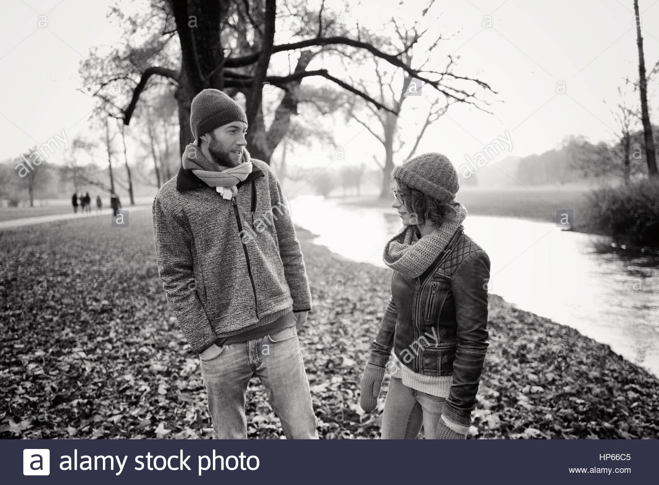 Young heterosexual couple autumn leaves river 30s - Stock Image