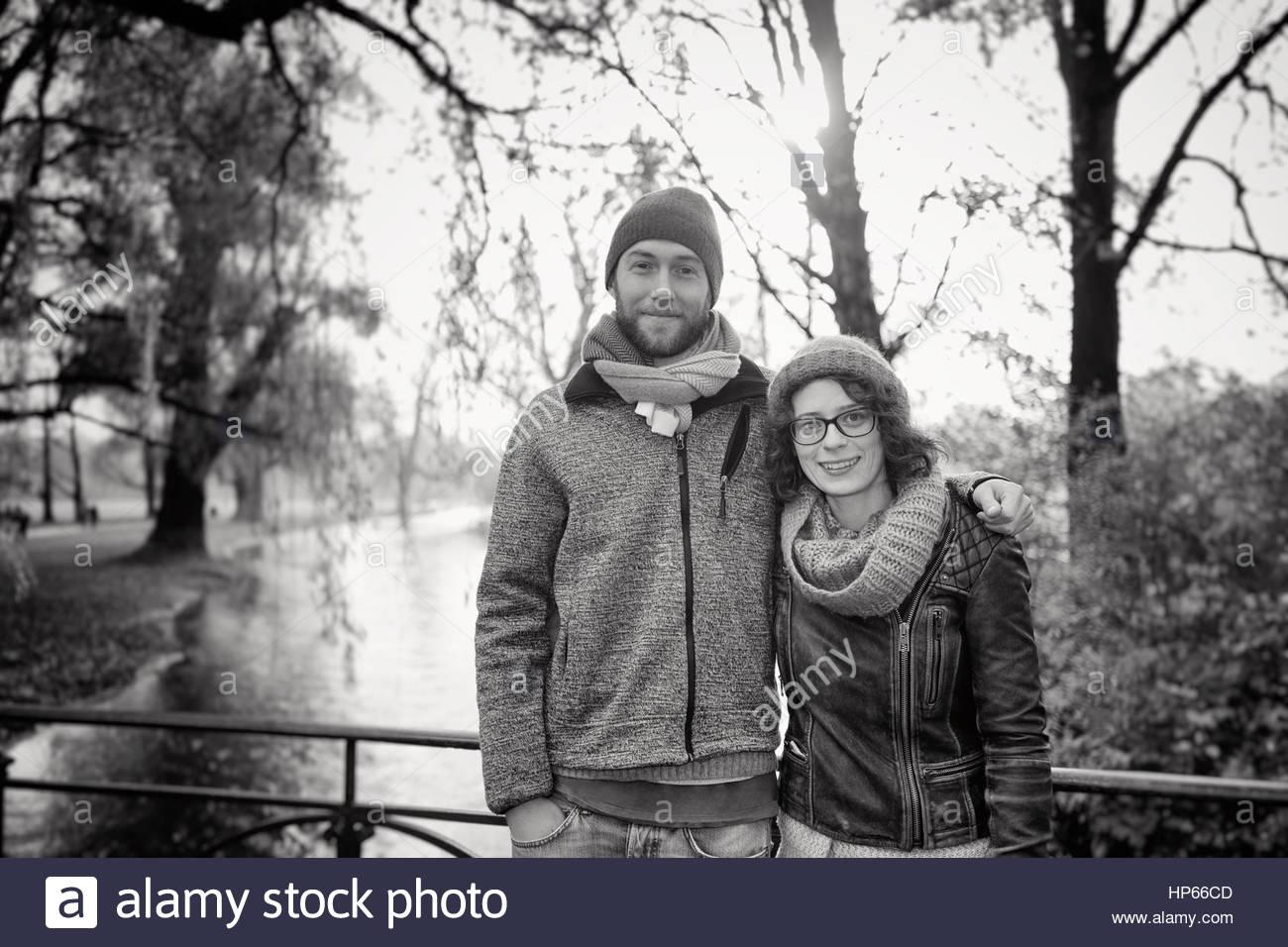 Heterosexual couple bridge hugging smiling 20s 30s - Stock Image
