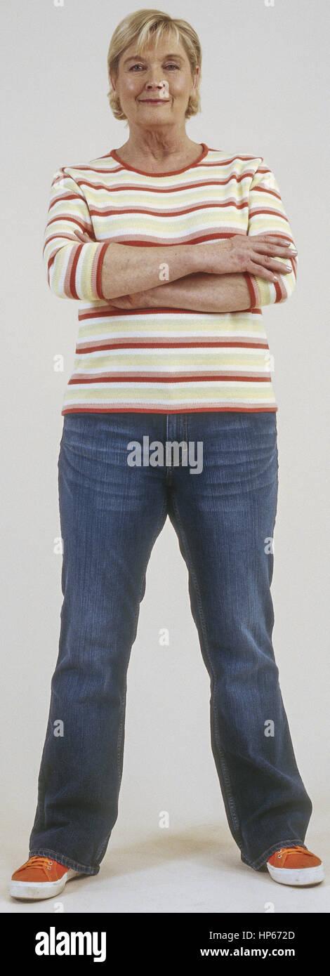 Seniorin in Jeans und Pulli, verschraenkte Arme (model-released) Stock Photo