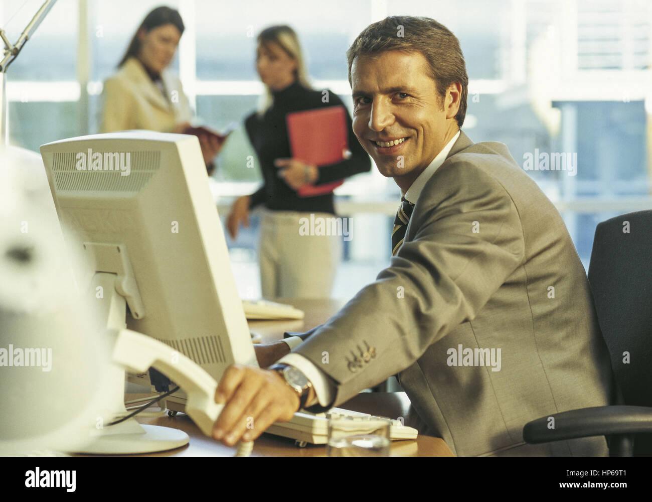 Manager am Schreibtisch, legt Telefonhoerer auf (model-released) - Stock Image