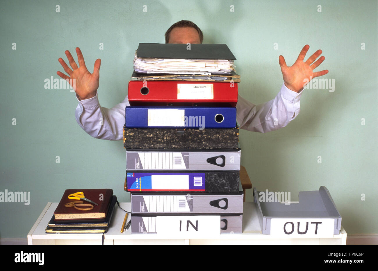 stressed businessman buried behind giant mound of paperwork in office - Stock Image