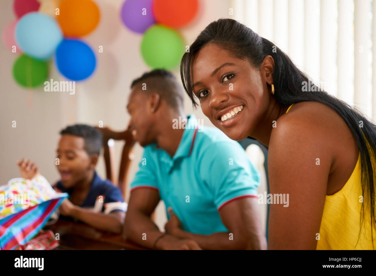 Happy black family at home. African american father, mother and child celebrating birthday, having fun at party. - Stock Image