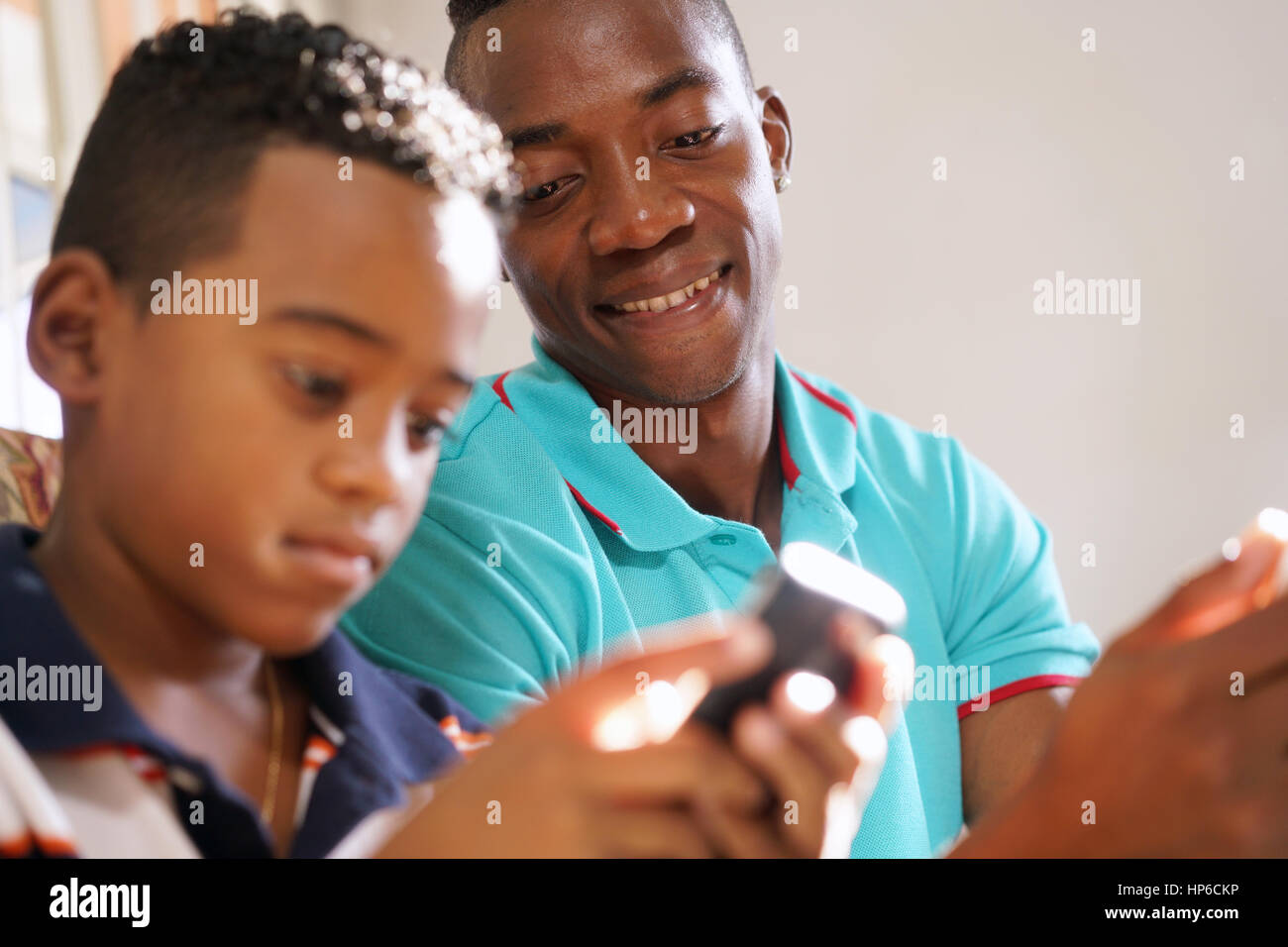 Happy black family at home. African american father and child playing game with cell phone. Hispanic dad and son - Stock Image