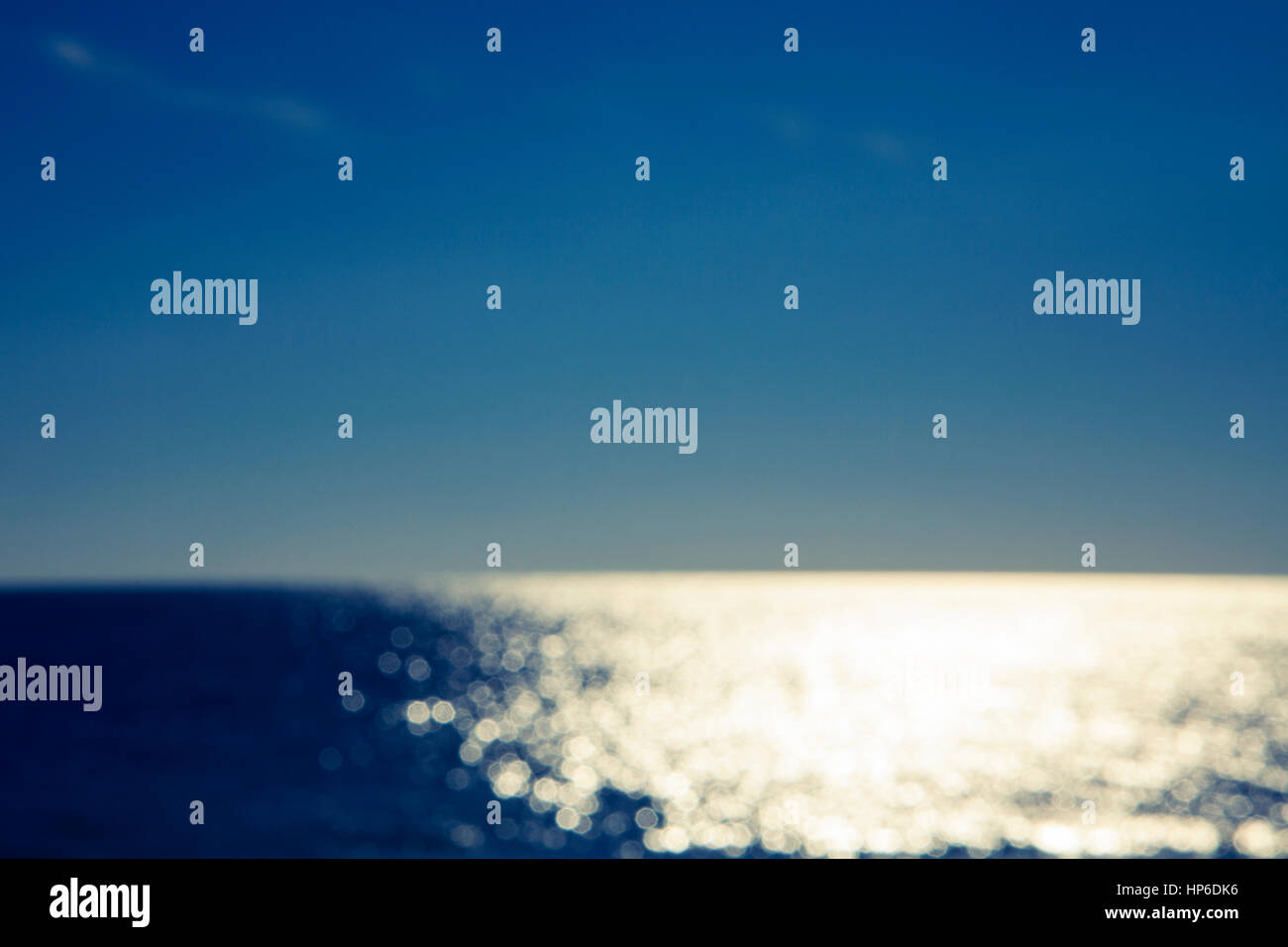 Blurred abstract ocean background. Sunlight reflecting on water. Bokeh effect. - Stock Image