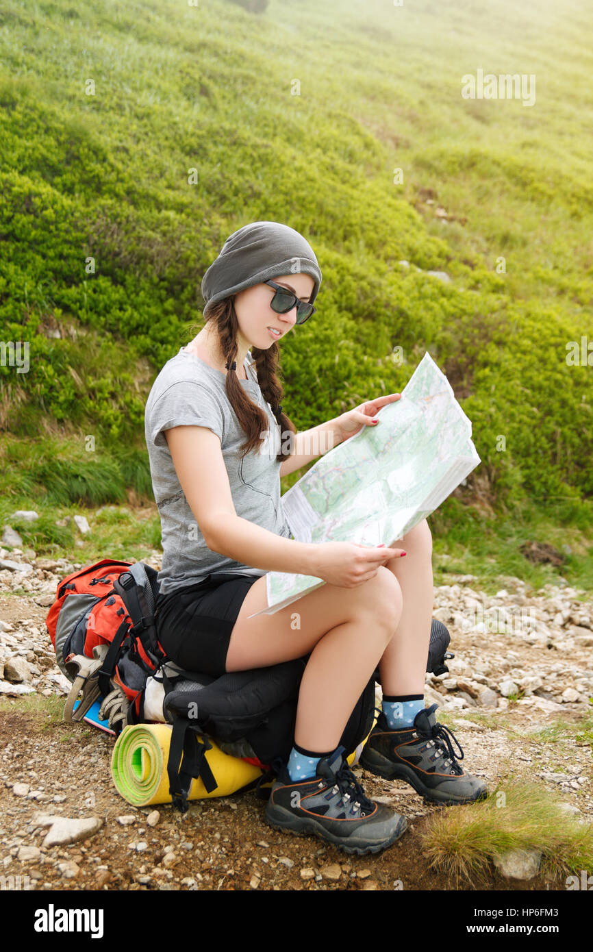 Girl tourist in mountain with sunshine read the map. Hiker watching the map. Girl tourist with map. Lifestyle concept - Stock Image