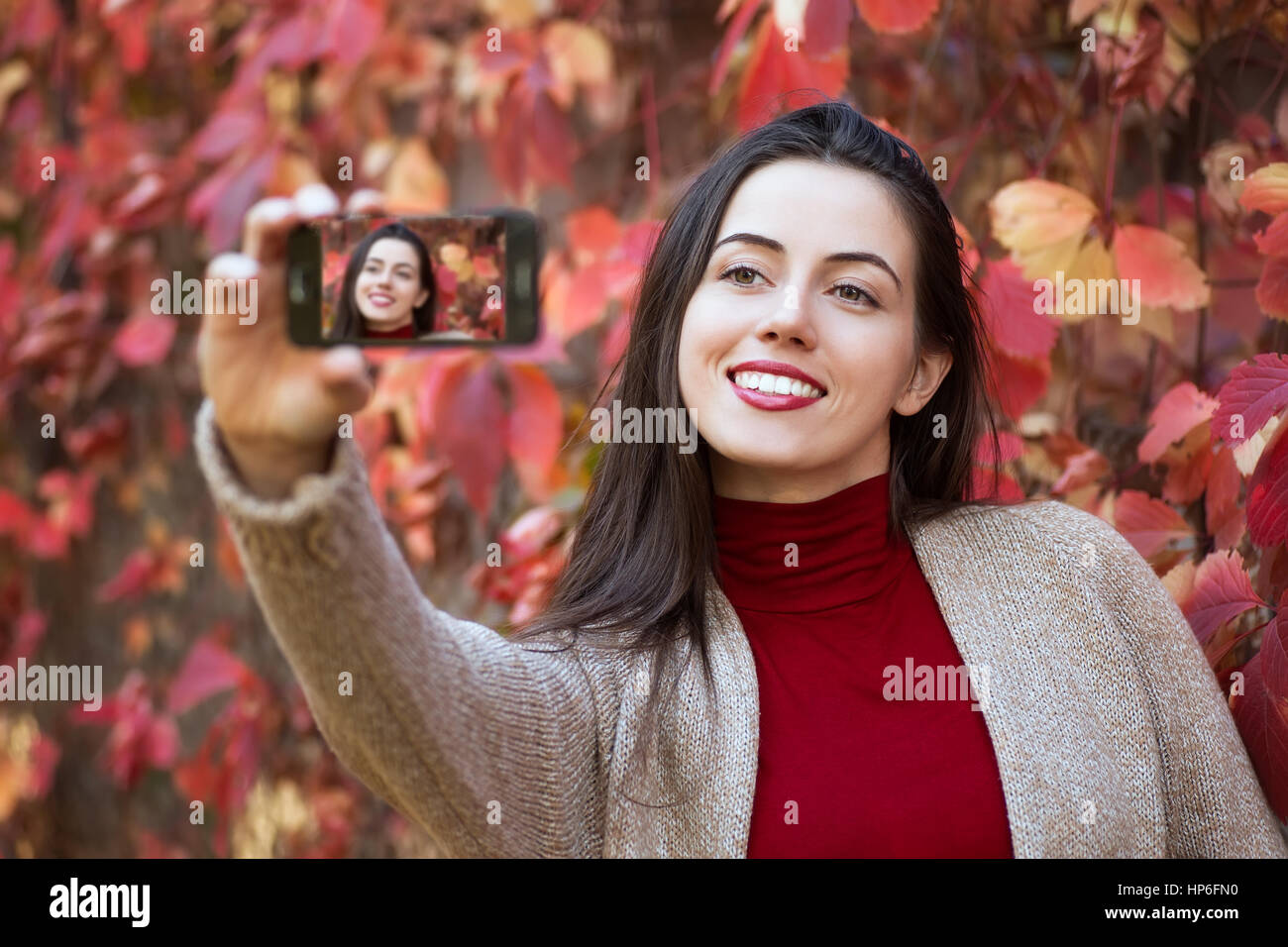 Beautiful young brunette caucasian woman taking selfie with smartphone outdoors in park in autumn. Selfie autumn. - Stock Image