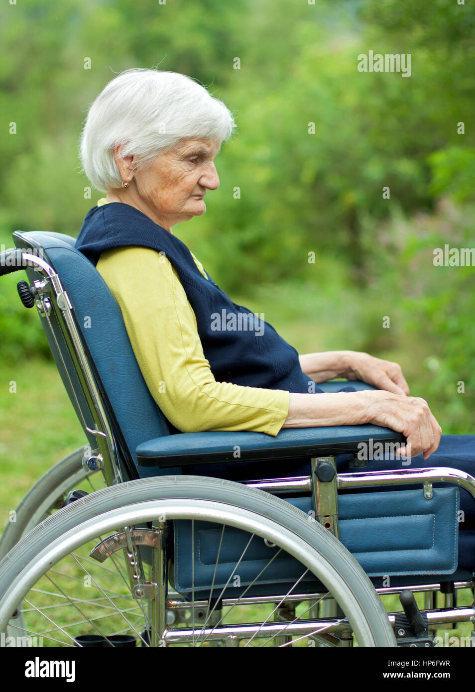 Handicapped sad elderly woman sitting in a wheelchair - Stock Image