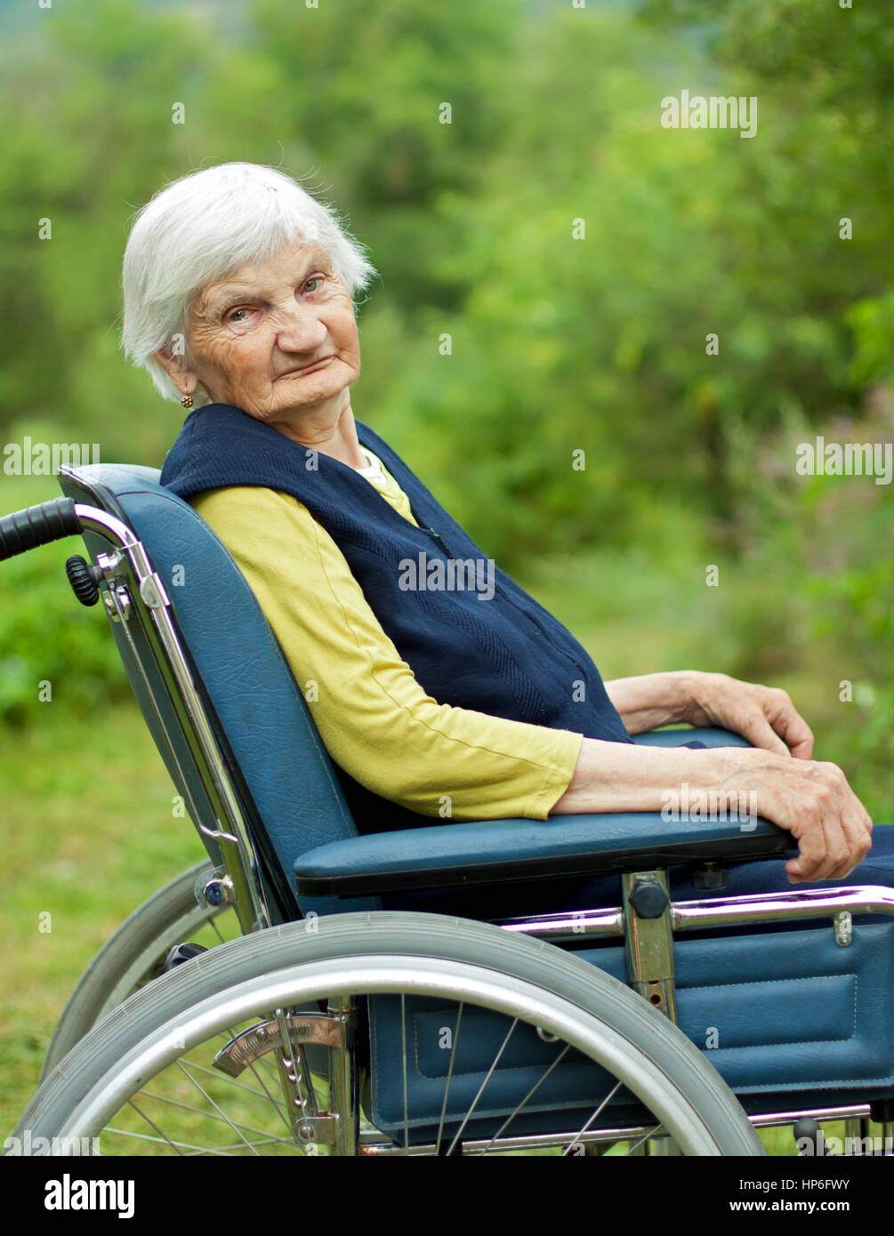 Handicapped elderly woman sitting in a wheelchair - Stock Image