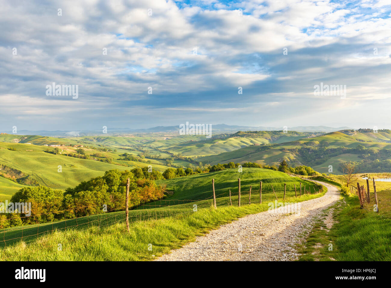 Rural view of the valley with a rolling landscape and a dirt road in Tuscany, Italy Stock Photo