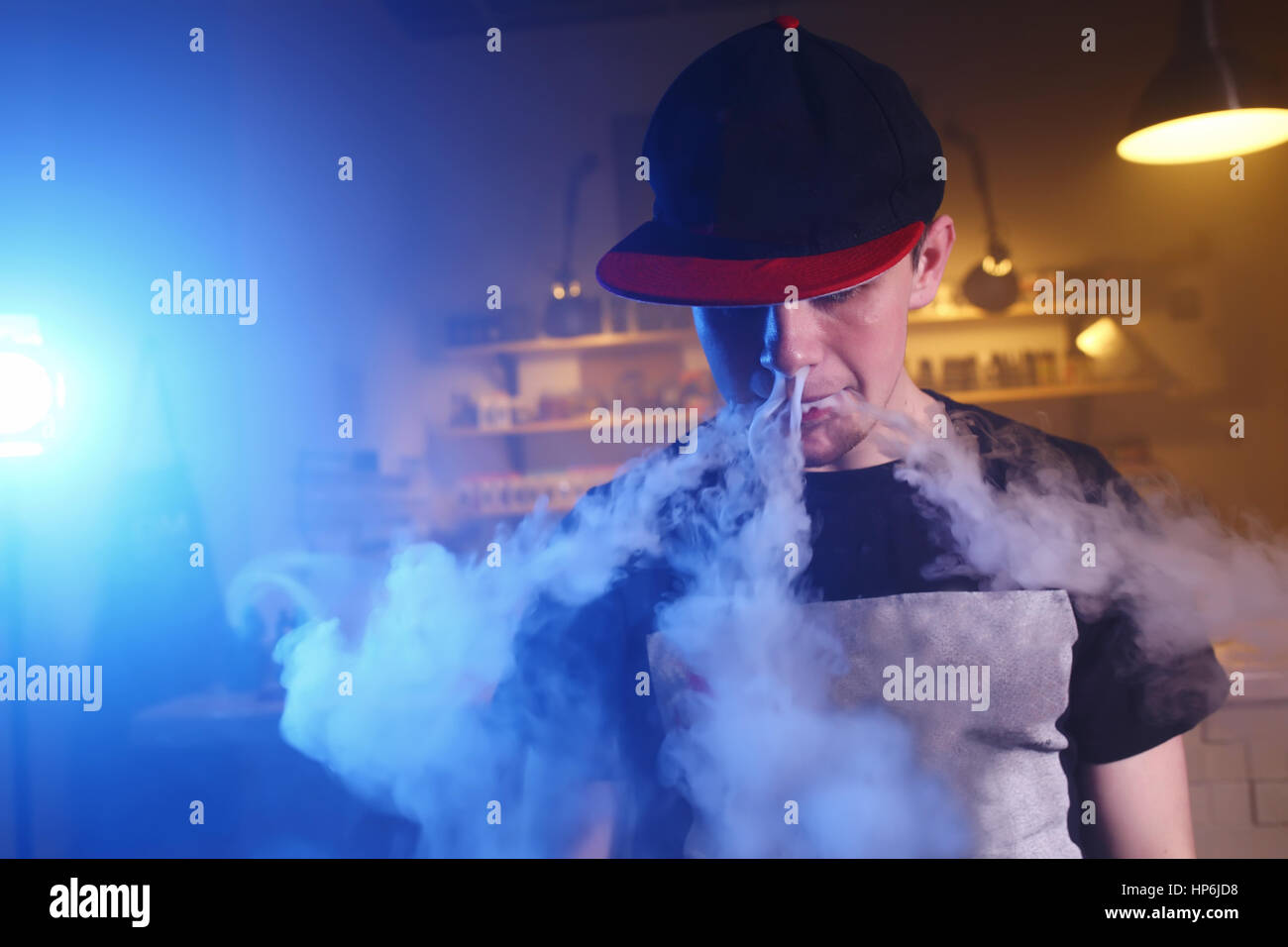 The man smoke an electronic cigarette at the vape shop. - Stock Image