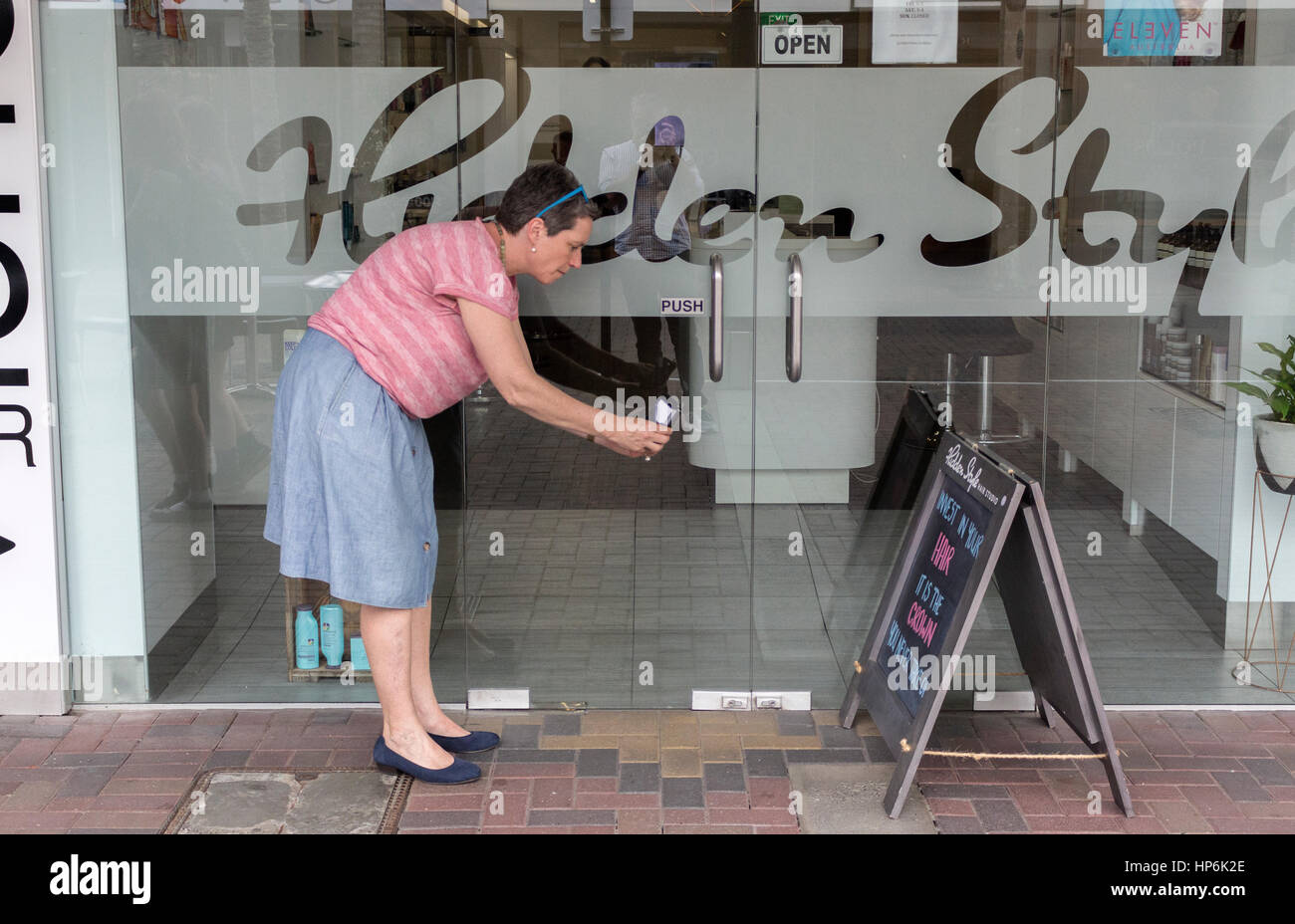 Woman with short hair is taking a photo of a funny sandwich board on the street 'Invest in your hair' - Stock Image