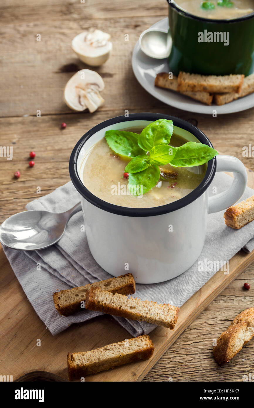 Mushroom soup with croutons and basil in metal mug on rustic wooden background - healthy organic homemade vegetarian - Stock Image