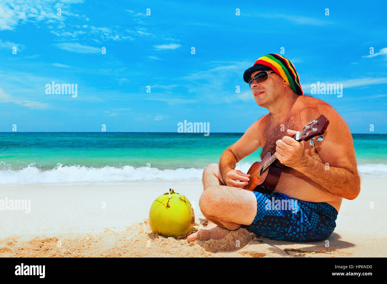 Happy retiree age man in funny hat has fun, play reggae music on Hawaiian guitar, enjoy caribbean beach party. Seniors - Stock Image