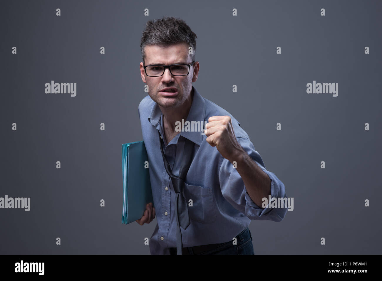 Angry untidy businessman with files snarling with fist raised - Stock Image