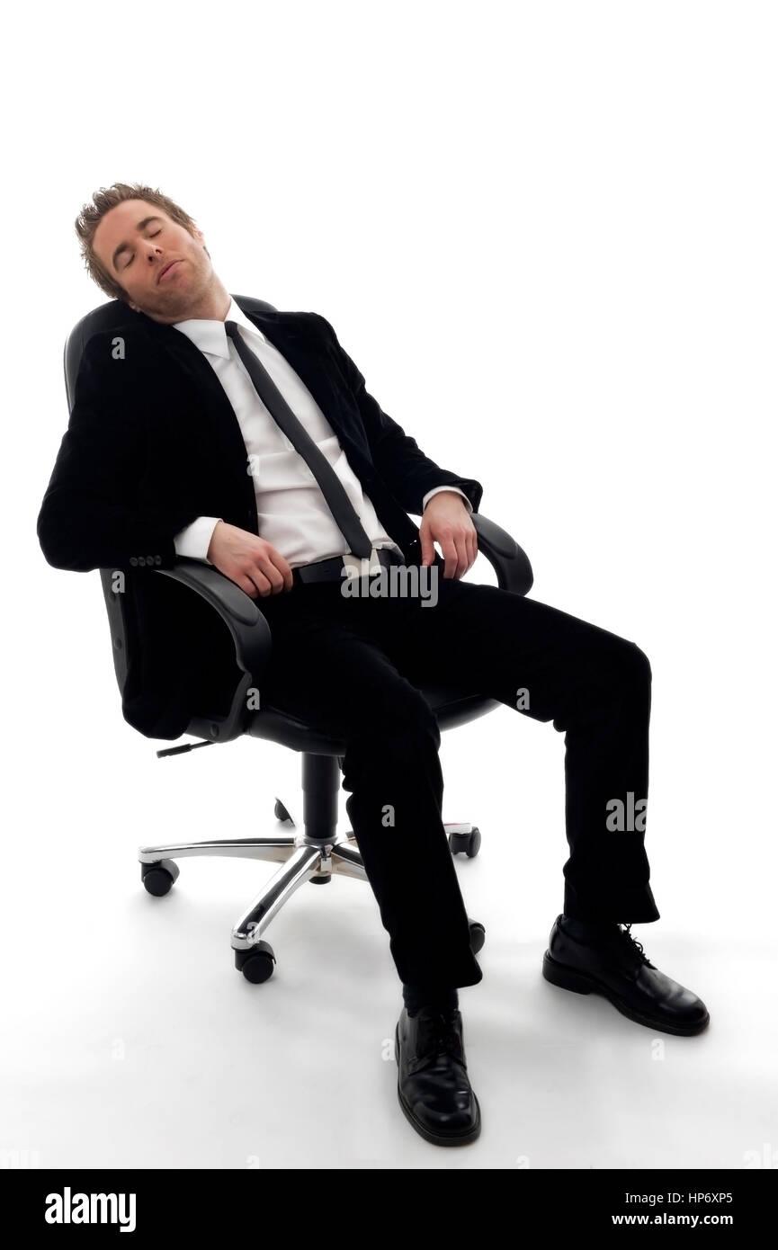 Junger Geschaeftsmann sitzt am Buerostuhl und schlaeft - businessman sleeping Stock Photo