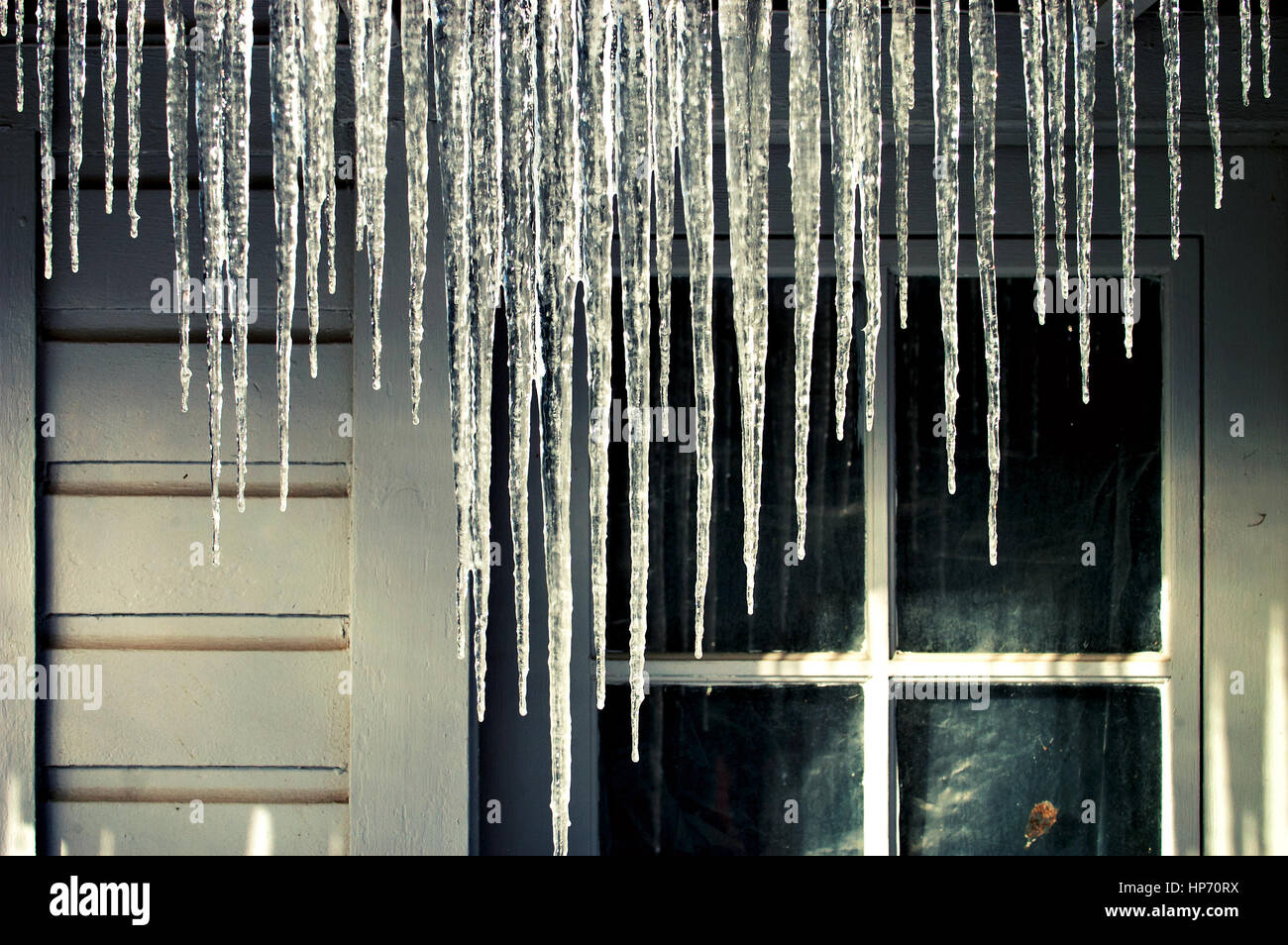 Icicles hanging from a house gutter in the winter. Stock Photo