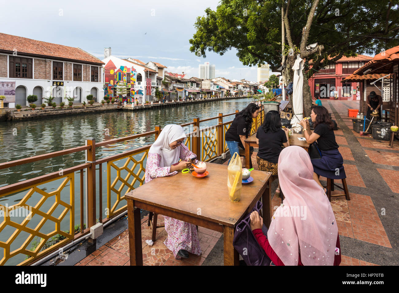 MELAKA, MALAYSIA: Two young Malaysian women, wearing the muslim hijab (veil) eat an ice cream in the colonial old - Stock Image