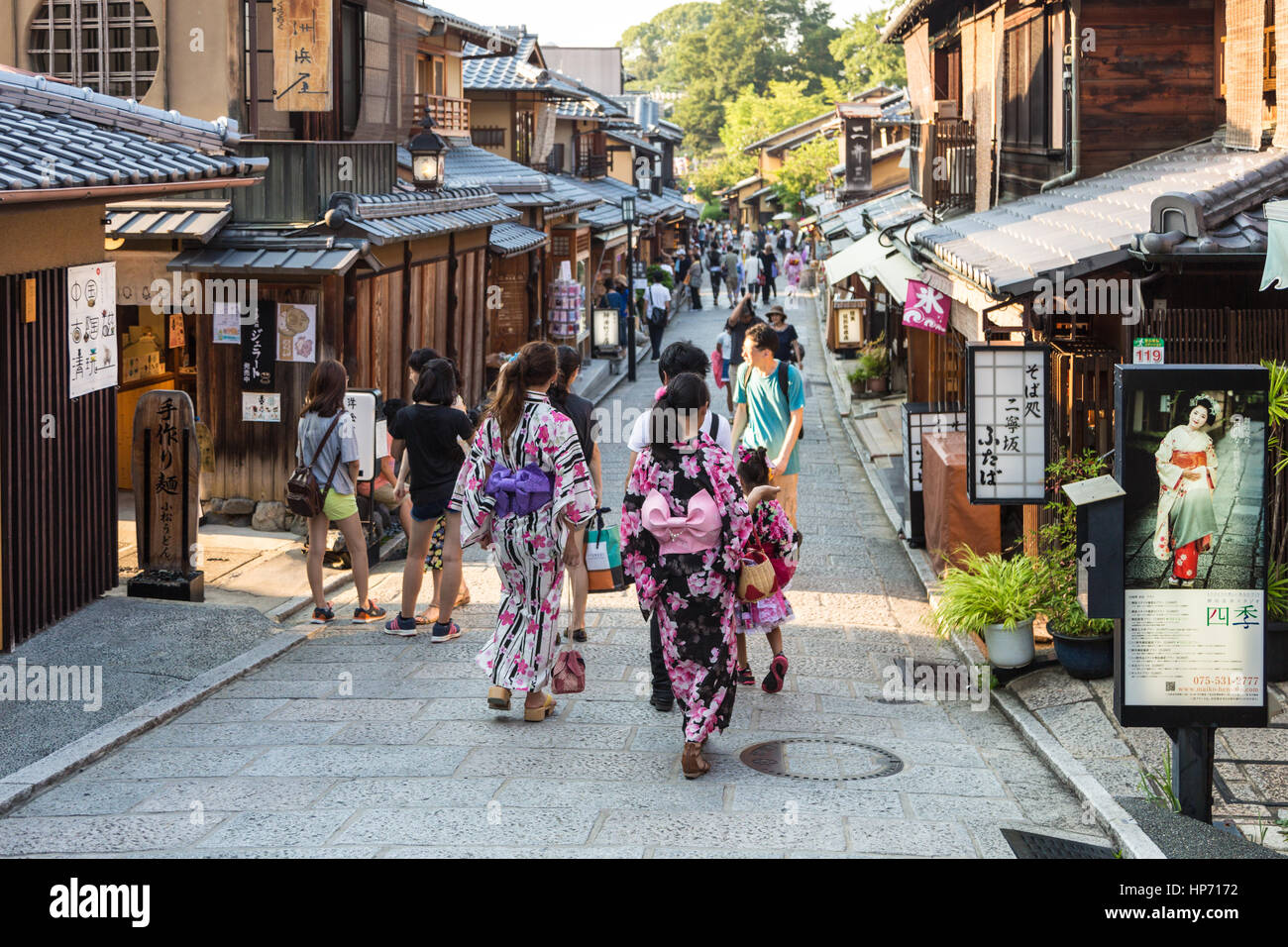 KYOTO, JAPAN - AUGUST 11, 2015: Young women wearing traditional Japanese Kimono walk in the street of Gion, Kyoto Stock Photo