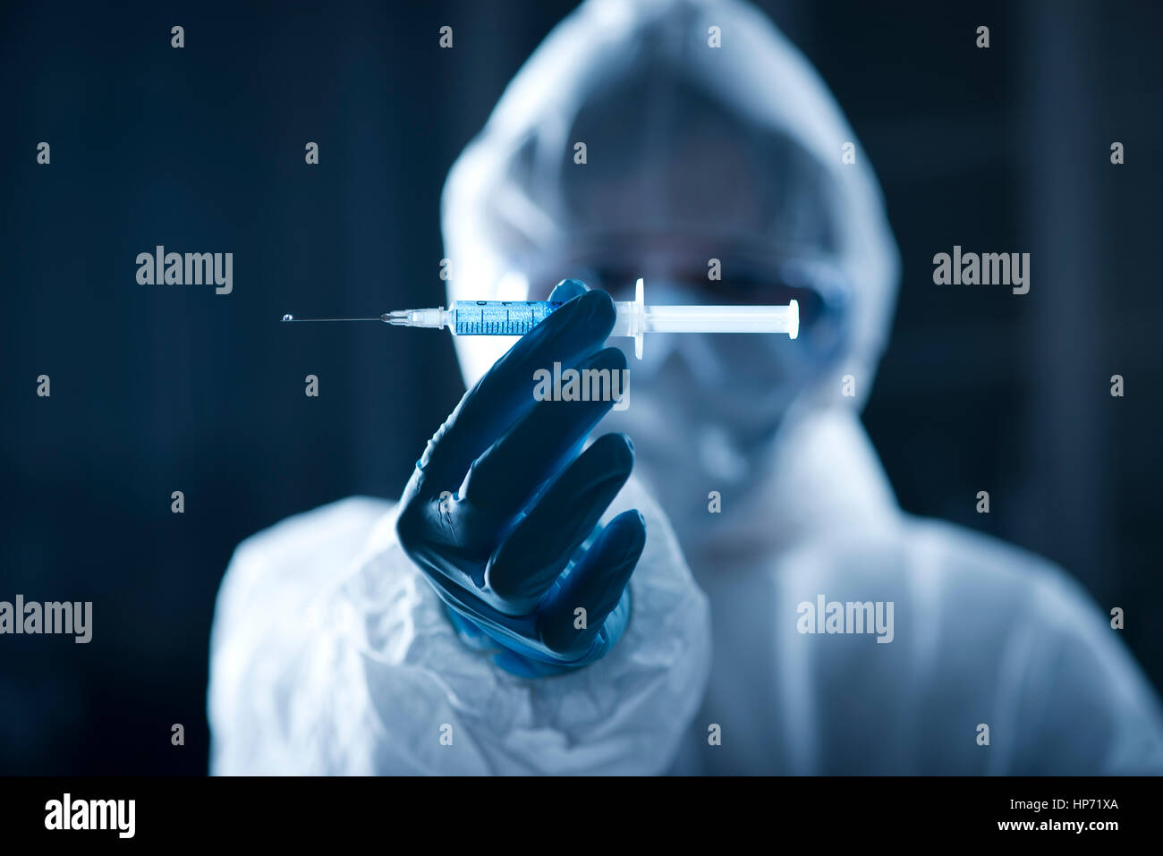 Researcher in hazmat protective suit preparing a syringe for injection. - Stock Image