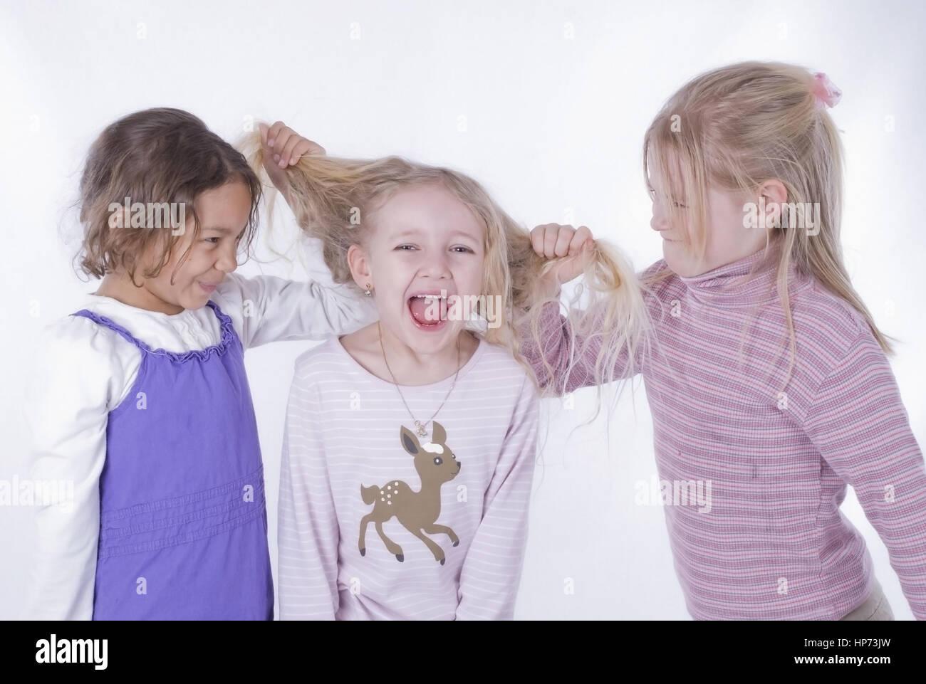 Model released, Zwei Maedchen reissen blondes Maedchen an den Haaren - girls in quarrel Stock Photo