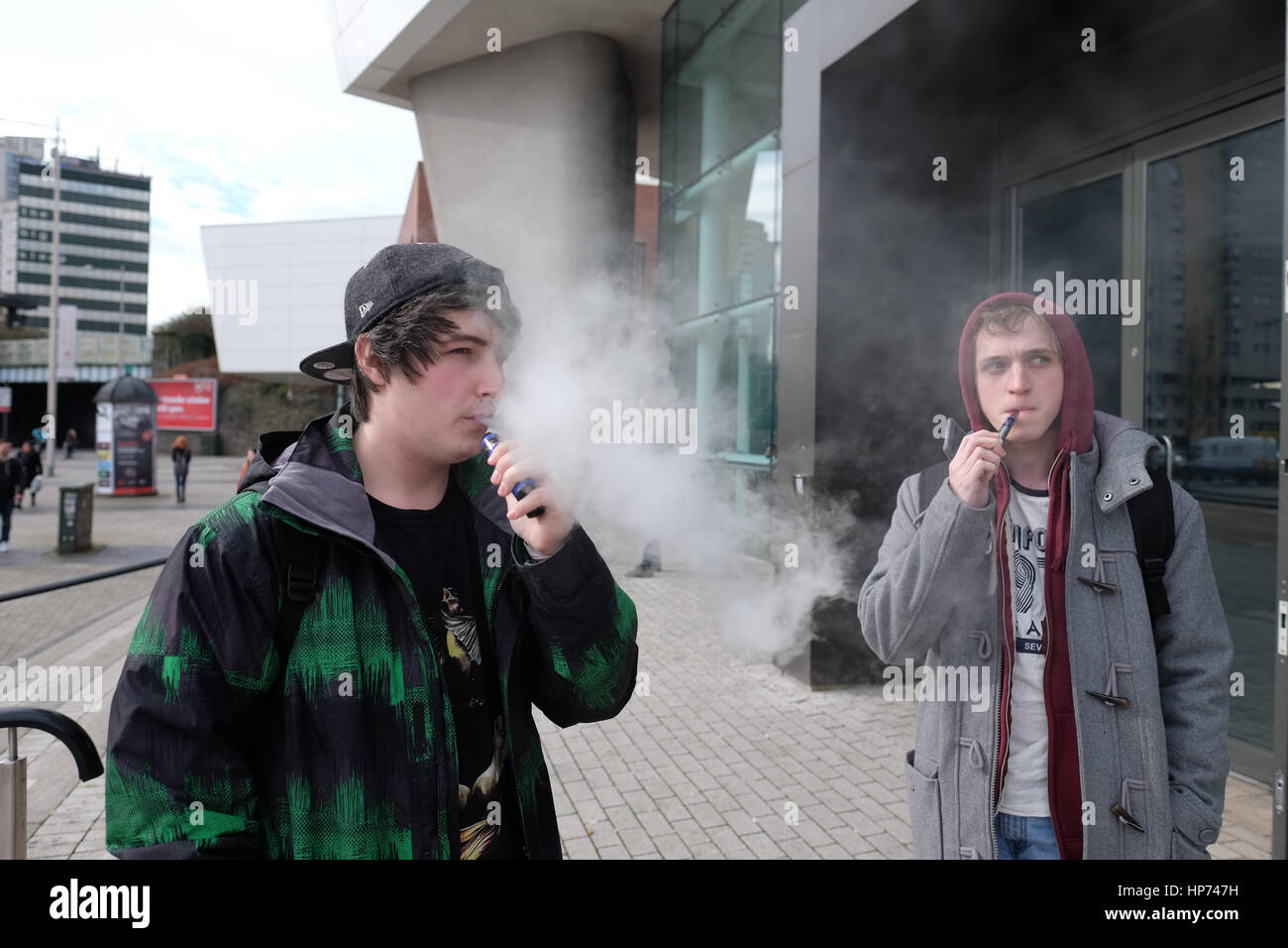 Carrie Edwards (left) 22 of age and Andrew Shaw (right) (22), USW Music Industry students, smoke e-cigarette during - Stock Image