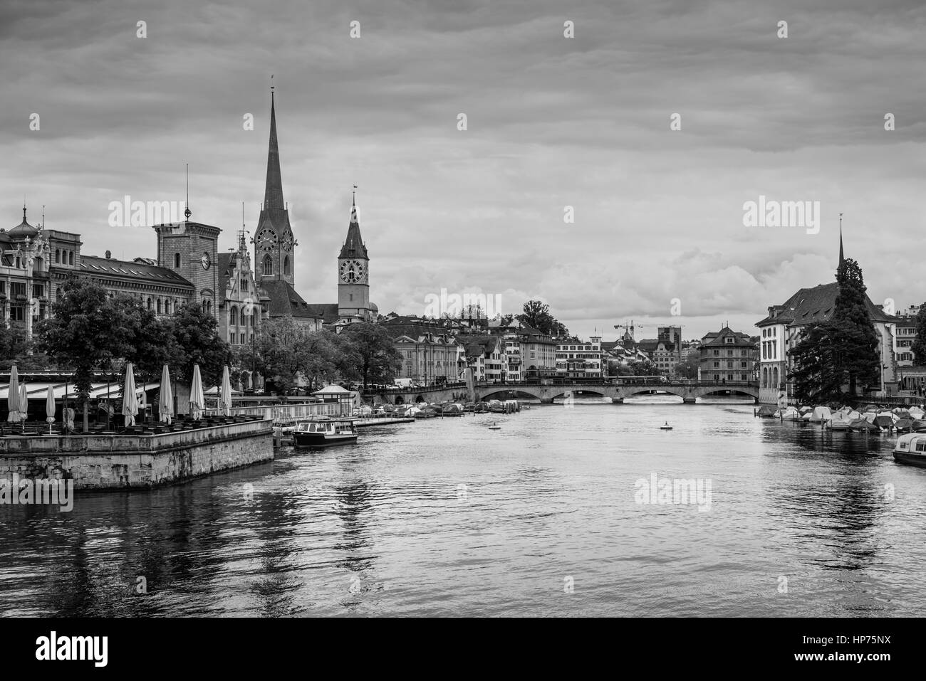 View of historic Zurich city center with Fraumunster Church, Munsterbrucke bridge and Limmat river on a cloudy rainy - Stock Image