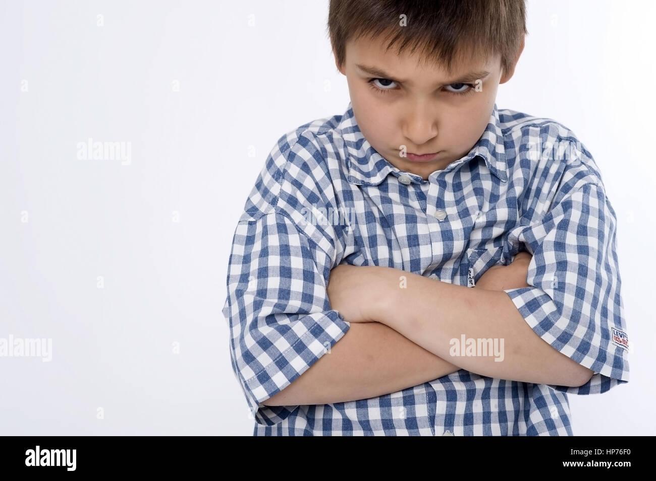 Model released, Junge, 8, mit boesem Blick und verschraenkten Armen - angry boy Stock Photo