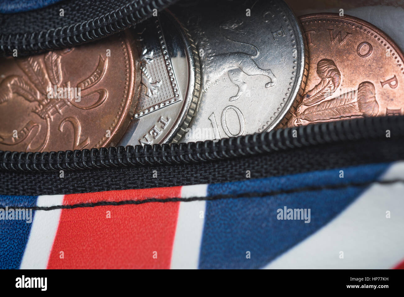 Zippered Union Jack coin purse with British coins / coinage visible. Metaphor for pennies, household spending, the - Stock Image
