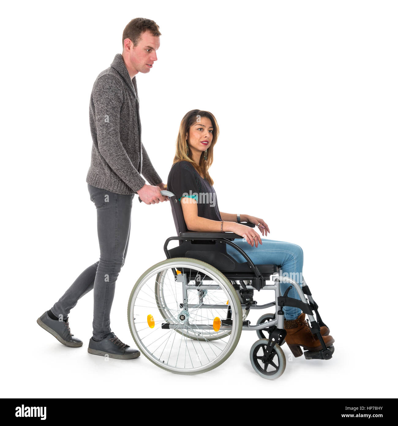 Man Pushing Woman In A Wheelchair Isolated On White
