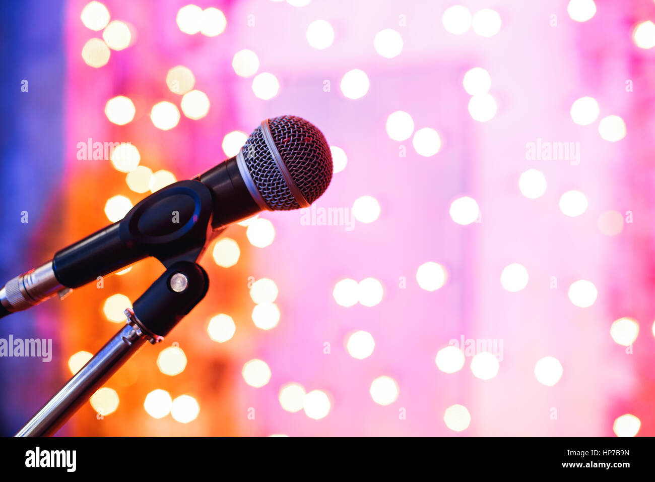 Close up of microphone in concert hall with blurred lights at background - Stock Image