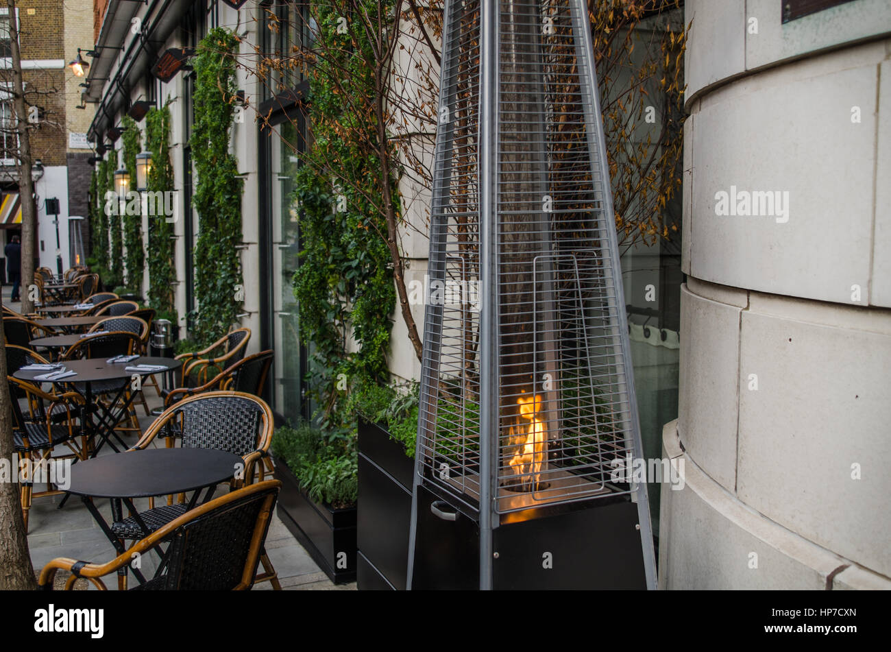 front of the restaurant, tables outside for customers prepared, gas lamp for heating, green plants on the wall - Stock Image