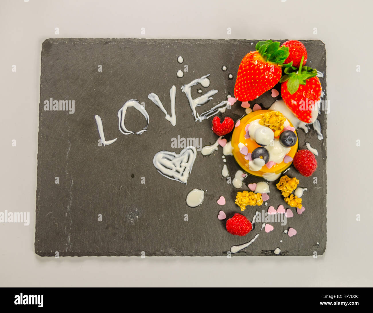 dessert with fruit on a black stone plate with an inscription love