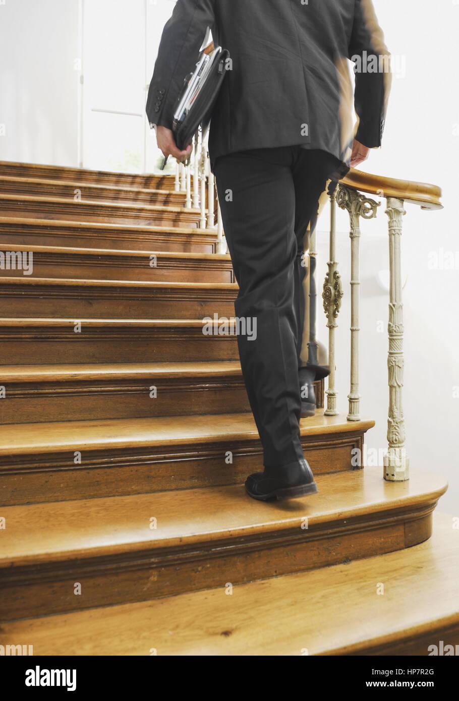 Mann mit Aktentasche geht Holztreppe hinauf (model-released) Stock Photo
