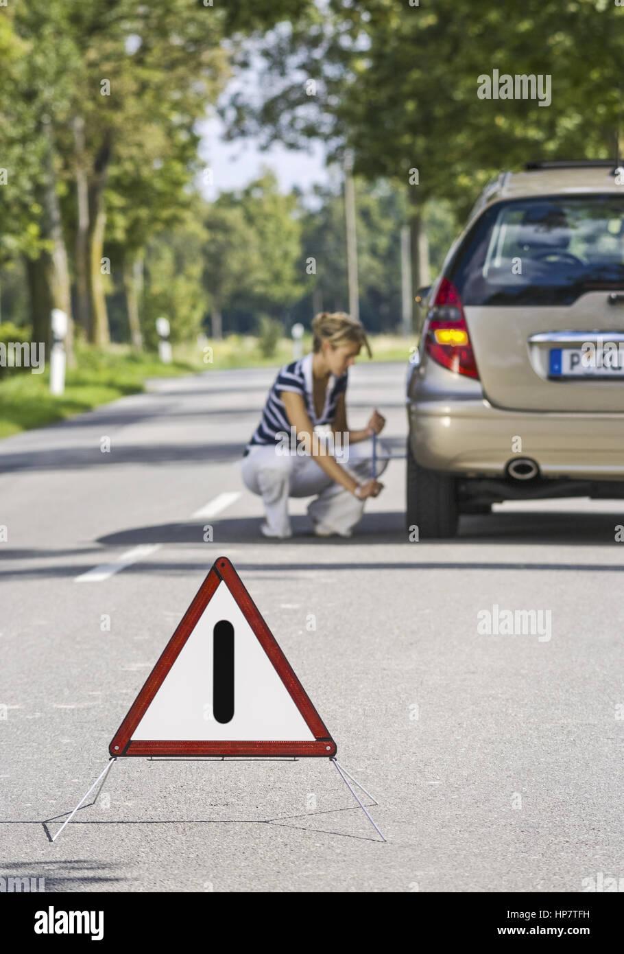 Frau mit Autopanne beim Reifenwechsel, Warndreieck (model-released) Stock Photo