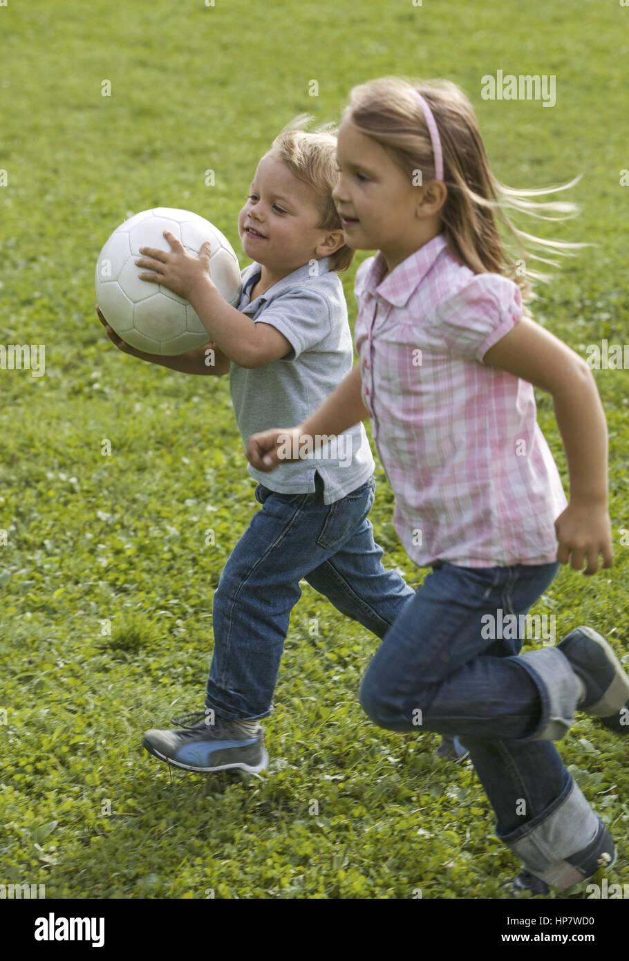 Kleiner Junge und Maedchen rennen mit Fussball ueber Wiese (model-released) - Stock Image