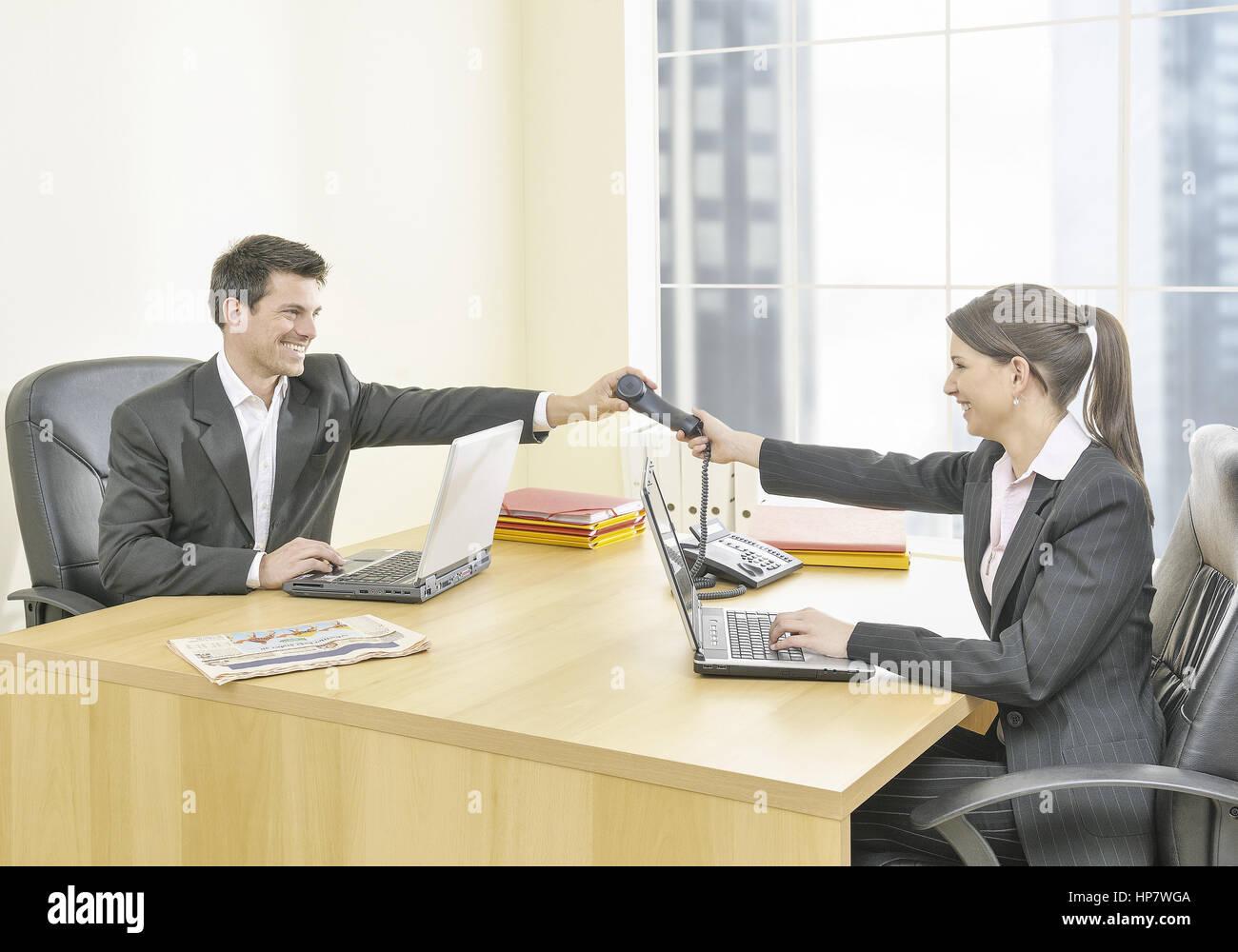 Frau und Mann im Buero, sie reicht ihm Telefonhoerer (model-released) - Stock Image