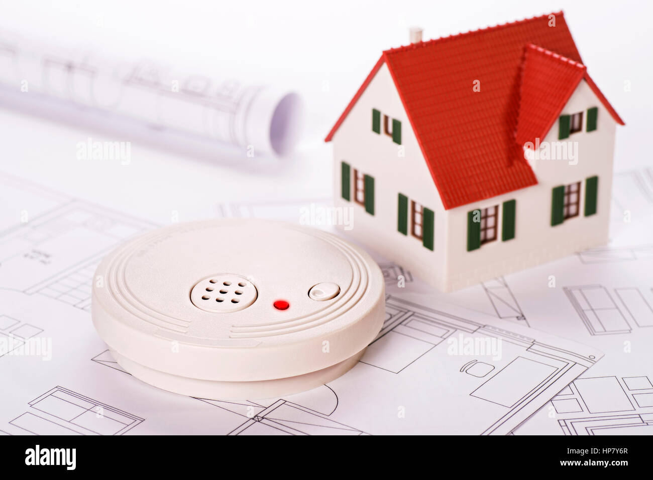 Smoke detector with house and blueprints Stock Photo
