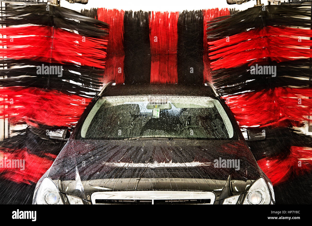 A black car is cleaned in a Gantry car wash. - Stock Image