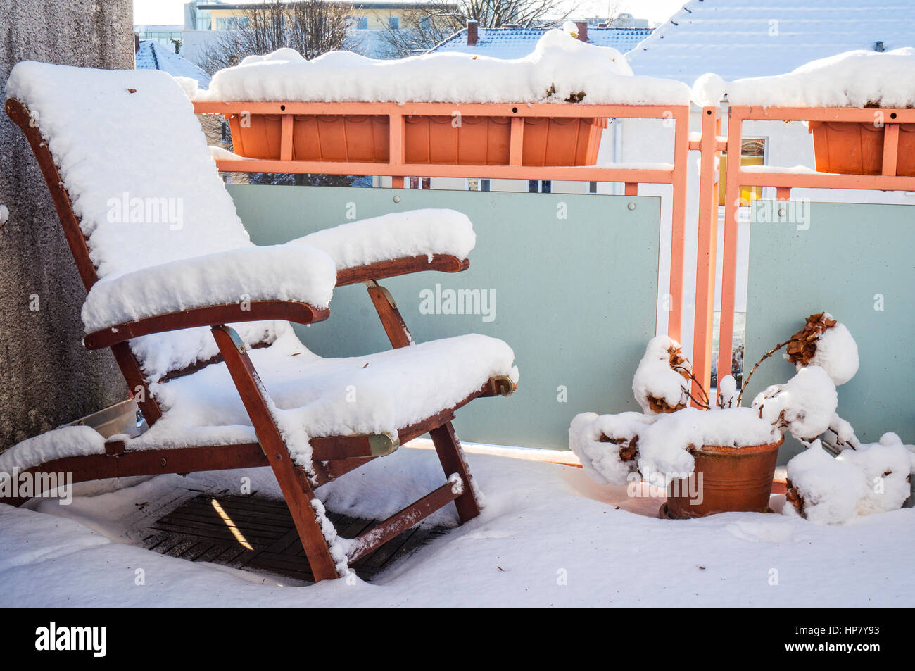 Snow covereddeck deck chair stands in winter on a snowy balcony - Stock Image