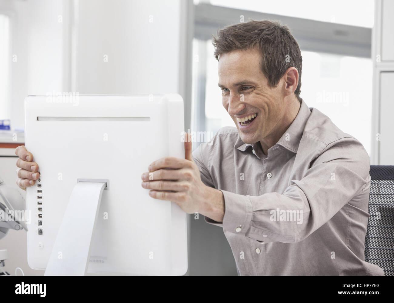 Mann packt erfreut seinen Bildschirm (model-released) - Stock Image