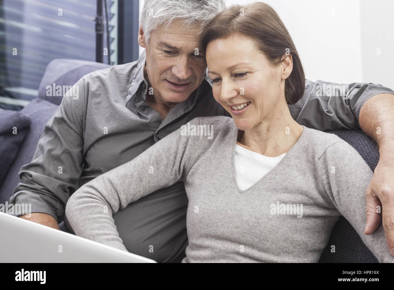 Paar sitzt auf Couch mit Laptop (model-released) Stock Photo